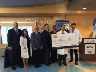Dr. Matthew Cascio accepts large check from Hyundai