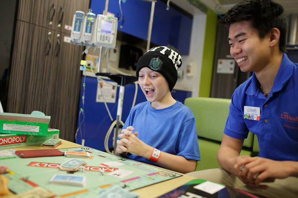 Young male patient playing a board game with counselor