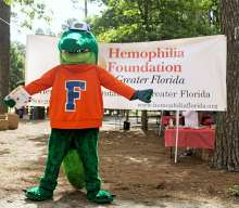 Gator mascot, Albert, standing in front of banner for the Hemophilia Foundation